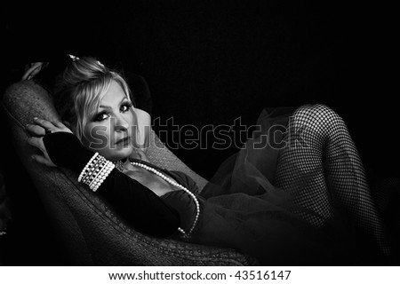 big eyed beautiful woman looking at viewer in old fashioned dress is reclining on sofa in this black and white image. - stock photo