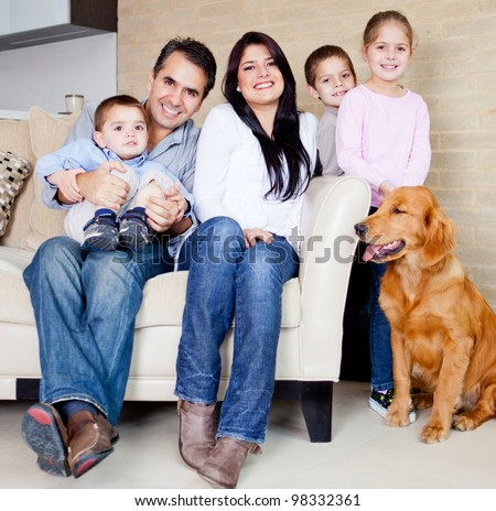 Big family at home with a dog, all looking very happy - stock photo