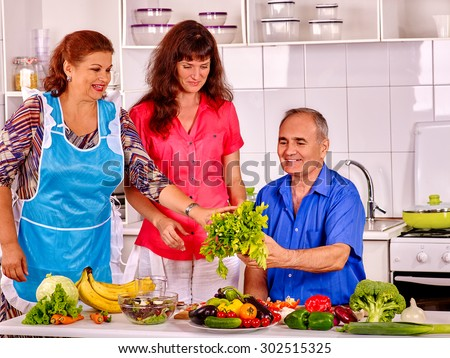 Big family cooking at kitchen. Grandfather and grandmother with adult daughter. - stock photo