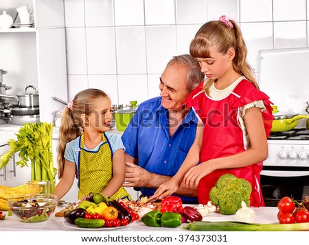 Big family cooking at kitchen. Grandfather preparing food with his children. - stock photo