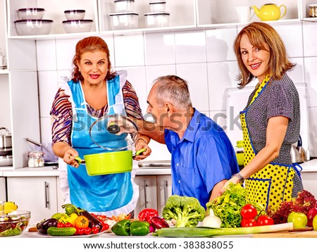 Big family cooking vegetarian soup at kitchen. Grandfather and grandmother. - stock photo