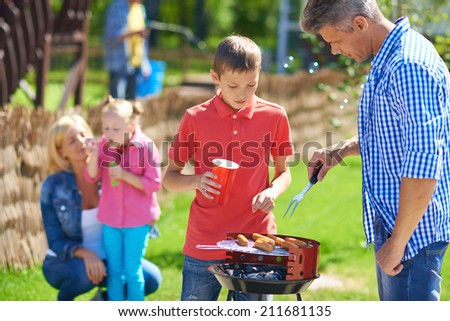 Big family frying sausages on grill - stock photo