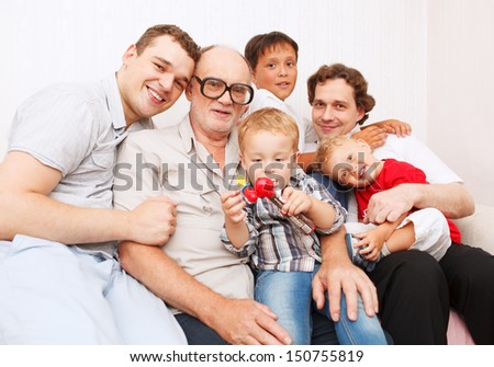 Big family. Generations. Men. Sitting on sofa smiling and looking to the camera.