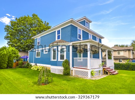 Big family house with church porch and doorsteps in front. Residential house with green lawn around and blue sky background. British Columbia, Canada. - stock photo