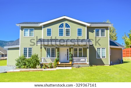 Big family house with pathway to the door in front and blue sky background. British Columbia, Canada.