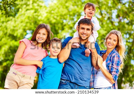 Big family looking at camera outdoors - stock photo