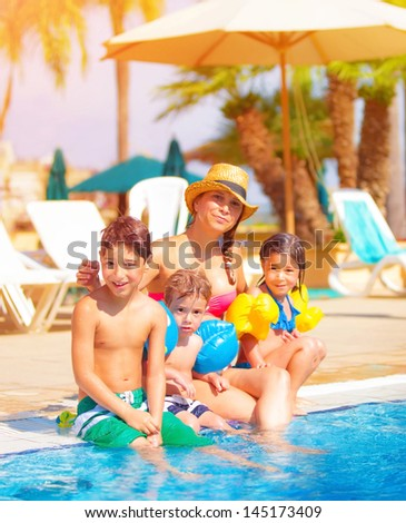Big family relaxed near poolside, happy young mother with three sweet child have fun outdoors on tropical resort, summer vacation, togetherness and love concept