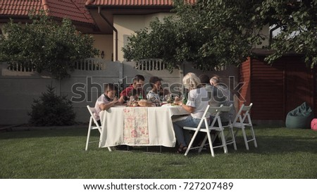 Big family sitting and having dinner together at table in the garden.