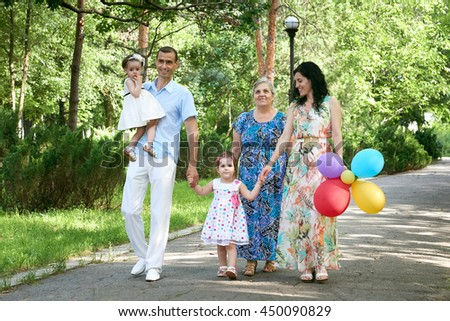 big family walk in summer city park, parents with child and grandmother, summer season, green grass and trees - stock photo