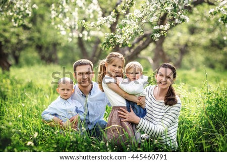 Big family with three little children. Parents and kids in spring garden. Mother, father, preschooler girl, toddler boy and baby.