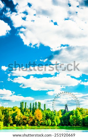Big ferris wheel in city park. Beautiful landscape with lake, trees blue sky, and clouds - stock photo