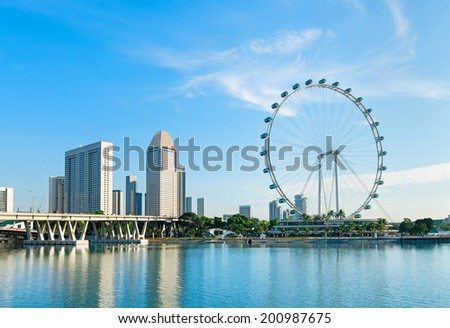 Big ferris wheel in the modern city skyline and bay water on front, Singapore.  - stock photo