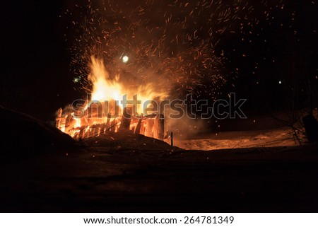 Big fire at night. Wood house ruins. Dark night. Light sparkles flying around the trees