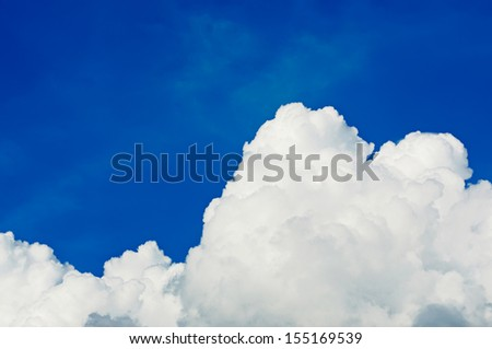 Big fluffy cloud against blue sky with copy space - stock photo