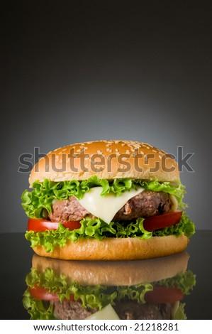 Big fresh delicious homemade hamburger with reflection - stock photo