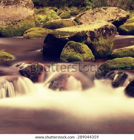 Big fresh green mossy boulders  in foamy water of mountain river. Light blurred cold water with reflections, white whirlpools in rapids. - stock photo
