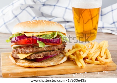 Big fresh  hamburger with french fries and beer - stock photo