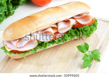 Big fresh sandwich on wooden board with some veggies on the background - stock photo