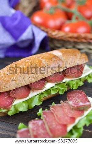 Big freshly made sandwich with lettuce , cheese and meat