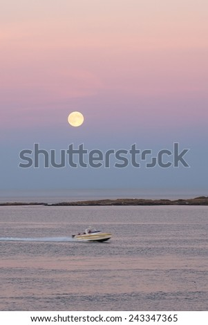 Big full moon is rising above the sea island in the Strait of Georgia at dusk - stock photo