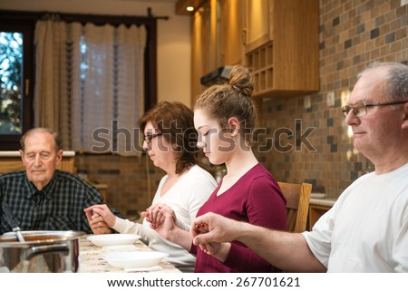 Big generation family having dinner together and holding each other by hands while praying. Focus on the young girl, natural light used. Horizontal composition; shallow depth of field - stock photo