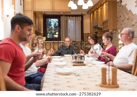 Big generation family having dinner together, holding each other by hands praying. Focus in the center of the frame on the grandpa, natural light used. Horizontal composition, narrow depth of field - stock photo