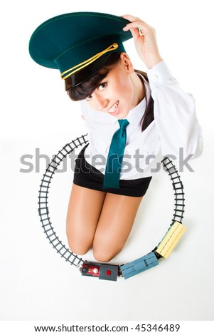 Big girl play railroad wearing formal clothes and staff locomotive driver cap