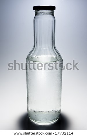 Big glass bottle half filled with water on gray background