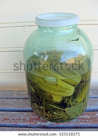 Big glass jar with pickled marinated cucumbers close up.