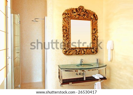 Big gold rustic mirror at contemporary bathroom - stock photo