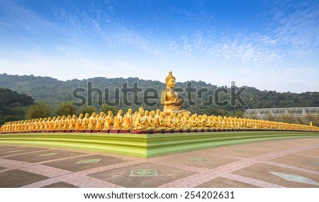 Big golden Buddha statue among many small Buddha statues in countryside public temple in Thailand - stock photo