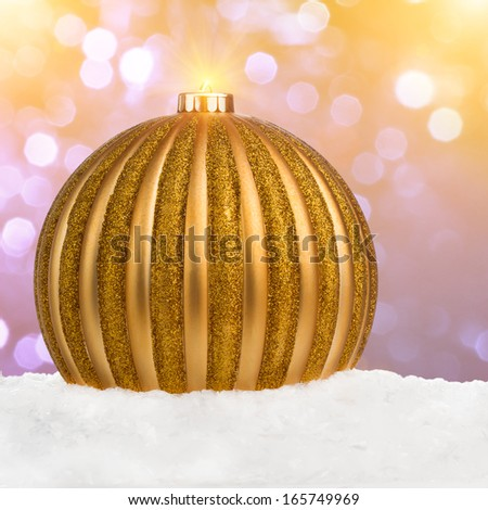 Big golden Christmas ball on snow over festive defocused background with copy-space - stock photo