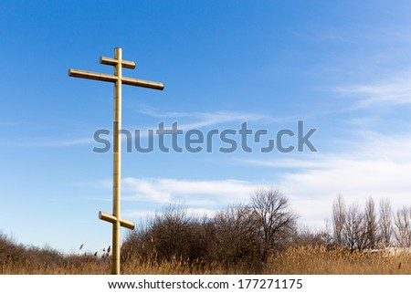 Big golden cross on a roadside with blue sky
