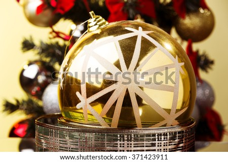 big golden xmas ball with snowflake placed on xmas tinsel , xmas tree for background  - stock photo