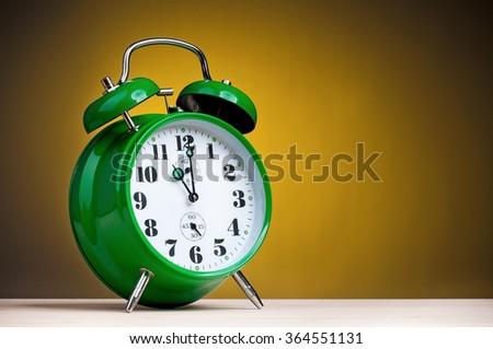 Big green alarm clock on dark yellow background - stock photo