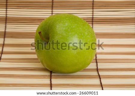 Big green apple on the wooden mat