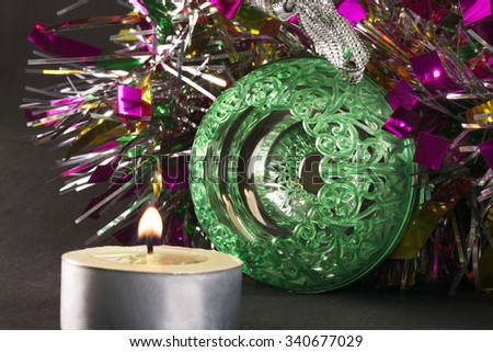 Big green carved mirror ball with a candle on a background of tinsel - stock photo