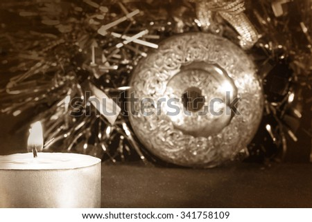 Big green carved mirror xmas ball with a candle on a background of tinsel, selective focus, vintage - stock photo