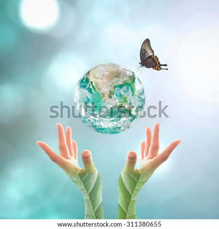Big green planet with butterfly over human hands in blurred cyan green bokeh background of natural tree leaves facing sun flare in vintage style color tone: Elements of this image furnished by NASA    - stock photo