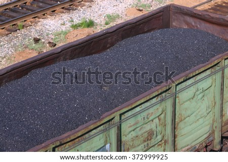 Big green Railway wagon loaded with coal at sunny day. Top view