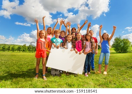 Big group of boys and girls holding blank banner showing blank placard board to write it on your own text, standing on the grass field on the park - stock photo