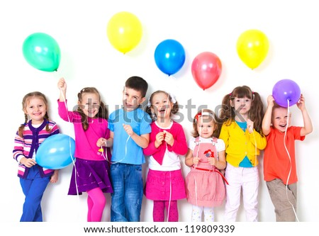 Big group of happy children with balloons at white wall - stock photo