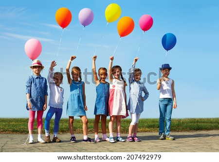 Big group of happy children with balloons on the street