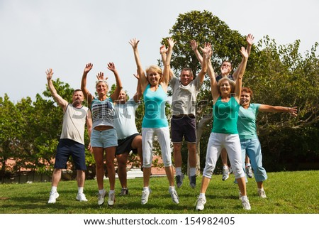 Big group of mature jumping people with hands up.  - stock photo