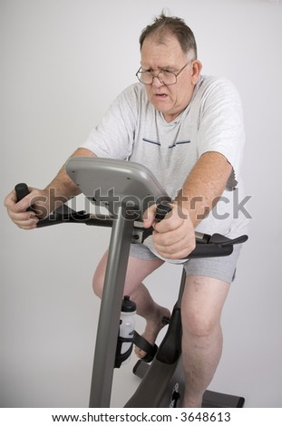 Big Guy working out on an exercise bike - stock photo
