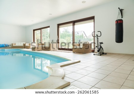 Big gym with swimming pool at luxury home - stock photo