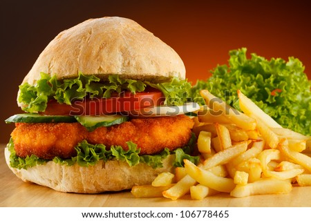 Big hamburger, French fries and vegetables - stock photo