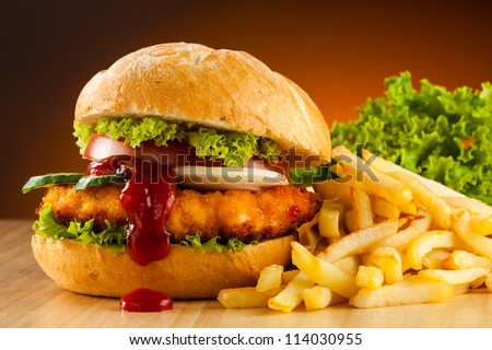 Big hamburger, French fries and vegetables