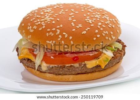 "Big hamburger from a natural whole beef with a slice of cheese ""cheddar"" on caramelized bun, seasoned with mustard, ketchup, onions, two slices of pickles, fresh lettuce, a slice of fresh tomato   - stock photo"
