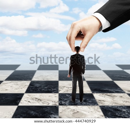 Big hand using tiny businessman as a pawn on chessboard. Sky background. Concept of control - stock photo